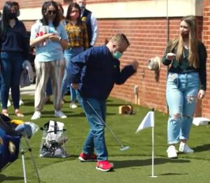 ETSU young man putting on gold course with friends